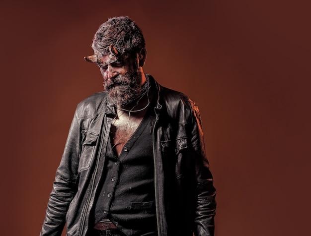 Inferno de halloween, perigo. demônio com barba, feridas, sangue vermelho em fundo marrom. homem com chifres de satanás.