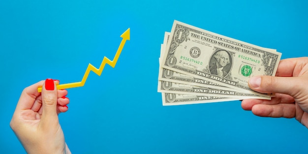 Inflação, hiperinflação do dólar. preços em alta. banner com fundo azul. uma nota de dólar na mão de um homem sobre um fundo azul. conceito de inflação.