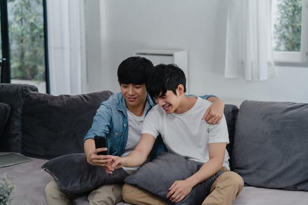 Influenciador asiático casal gay vlog em casa. os homens asiáticos lgbtq felizes relaxam o divertimento usando o upload do vídeo do vlog do estilo de vida do registro do telefone móvel da tecnologia nas mídias sociais ao encontrar o sofá na sala de estar.