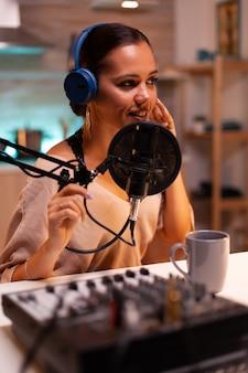 Influenciador criativo com fones de ouvido falando com os fãs ao vivo nas redes sociais usando equipamentos profissionais