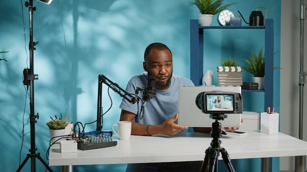 Influenciador de mídia social analisando laptop na câmera para podcast