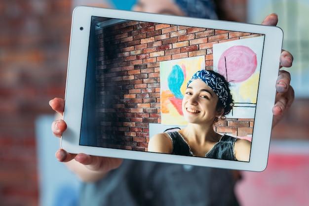 Influenciador de mídia social. artista talentosa usando um tablet para tirar selfie com suas obras de arte