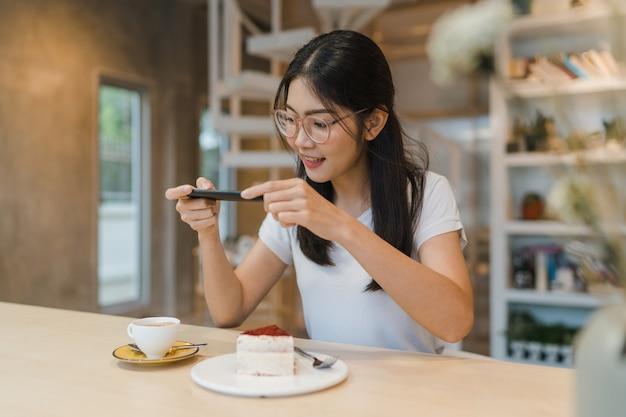 Influenciador de mulheres asiáticas amigáveis do blogger comem bolo em um café noturno