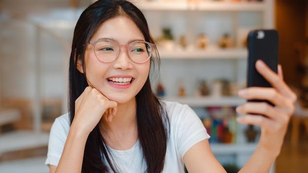 Influenciador de mulheres asiáticas amigáveis do blogueiro acenando com a mão fazendo videochamada em um café noturno