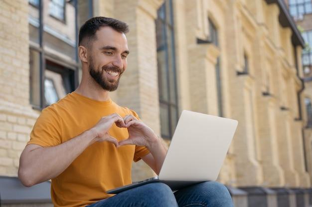 Influenciador de sucesso usando a comunicação do laptop online homem bonito e sorridente fazendo videochamada