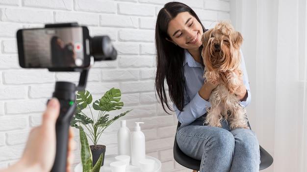 Influenciador feminino em casa com smartphone e animal de estimação