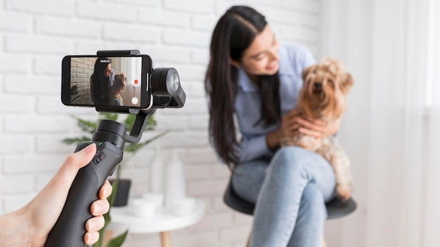 Influenciador feminino em casa com smartphone e cachorro