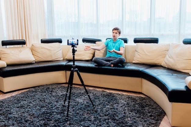 Influenciador ou adolescente do youtuber gravando um vídeo com o smartphone em casa