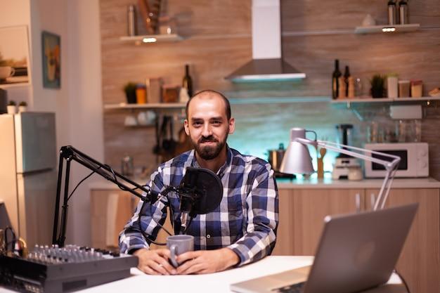 Influenciador segurando a xícara de café e gravando podcast em estúdio caseiro
