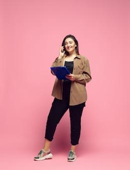 Influenciador sempre online jovem mulher em roupas casuais em fundo rosa bodypositive