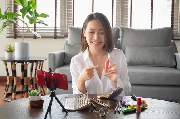 Influenciadora de beleza feminina fazendo um vídeo tutorial para seu canal de beleza sobre cosméticos durante a segurança em casa