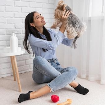 Influenciadora feminina em casa se divertindo com o cachorro
