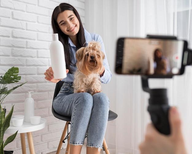 Influenciadora feminina em casa segurando cachorro e garrafa