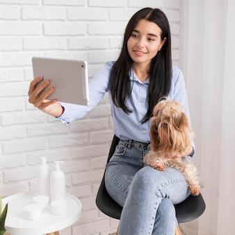 Influenciadora feminina em casa segurando cachorro e tablet
