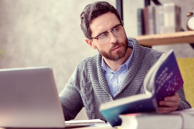 Informação importante homem barbudo sério olhando para o livro sobre astrologia enquanto faz seu trabalho