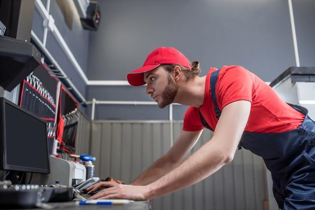 Informação importante. jovem adulto interessado em roupas de trabalho em pé olhando para o monitor do computador na oficina