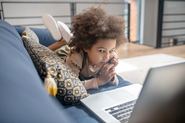 Informação interessante. menina afro-americana interessada com cabelo escuro e encaracolado olhando para o laptop deitado no sofá em casa