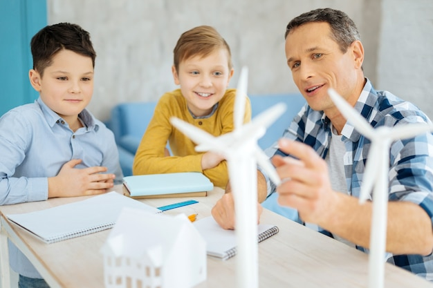 Informação interessante. pai simpático e otimista apontando para os modelos de turbina eólica em cima de sua mesa e discutindo sua construção com seus filhos curiosos