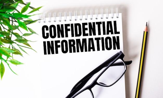 Informações confidenciais são escritas em um caderno branco ao lado de um lápis, óculos de armação preta e uma planta verde.
