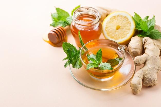 Infusão de bebida quente em copo para gripe fria nos dias de outono. xícara de chá de gengibre com hortelã, limão e mel em uma mesa de coral