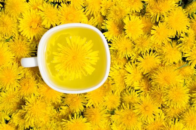 Infusão de chá flor dente de leão em copo branco vista superior