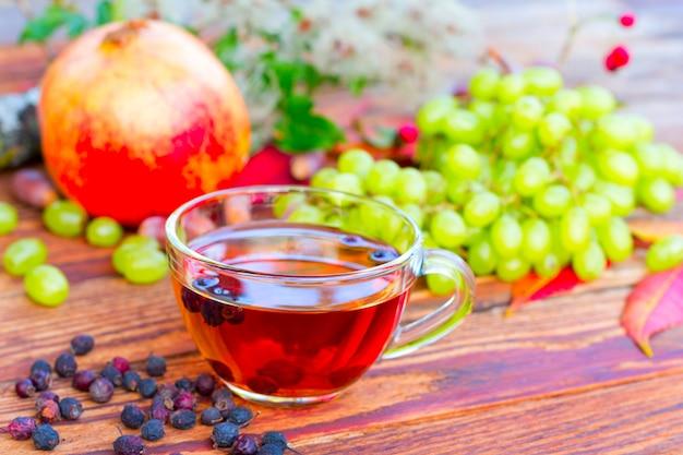 Infusão de frutas de espinheiro no fundo de uvas brancas, romãs e folhas de outono