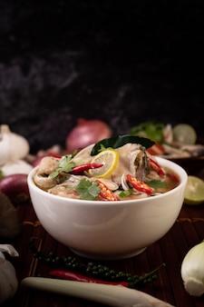 Infusão de peixe cozido com tomate, cogumelos, coentro, cebolinha e capim-limão em uma tigela