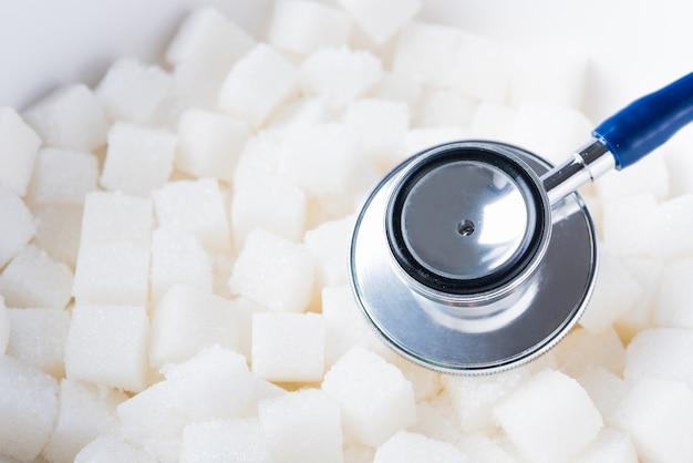 Ingrediente alimentar doce em cubo de açúcar e estetoscópio médico