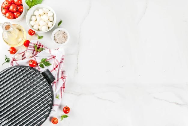 Ingrediente alimentar italiano de pizza de massa caseira na mesa de mármore branca com vista superior de farinha, azeite, manjericão, tomate e acessórios de cozinha