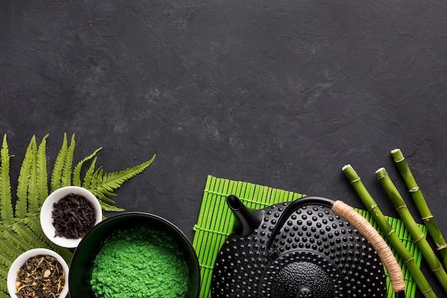 Ingrediente de chá de ervas crus com bule em fundo preto