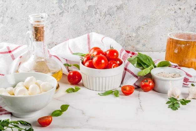 Ingrediente de comida italiana de pizza de massa caseira na mesa de mármore branca com farinha, azeite, manjericão, tomate e acessórios de cozinha