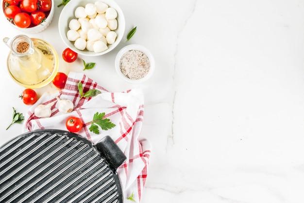 Ingrediente de comida italiana de pizza de massa caseira na mesa de mármore branca com vista superior de farinha, azeite, manjericão, tomate e acessórios de cozinha