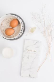 Ingrediente de cozimento saudável com o bloco de notas contra a superfície branca