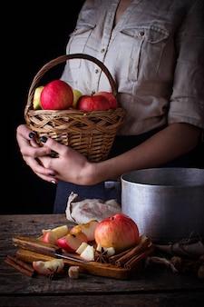 Ingrediente para cozinhar cidra ou compota e mulher com uma cesta de maçãs