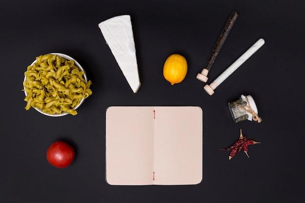 Ingrediente saboroso para fazer macarrão com diário em branco aberto na superfície preta