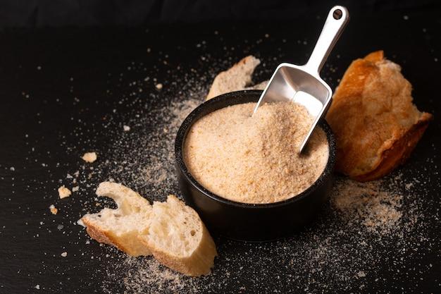 Ingredientes alimentares caseiros pão orgânico migalhas na tigela de cerâmica preta na placa de ardósia preta