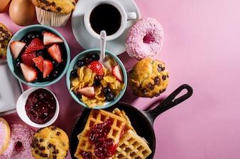Ingredientes alimentares deliciosos e frescos do café da manhã no fundo brilhante cor-de-rosa. Pronto para cozinhar. Conceito de culinária saudável para casa.