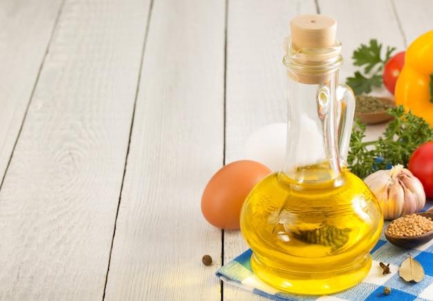 Ingredientes alimentares e óleo, especiarias em fundo de madeira