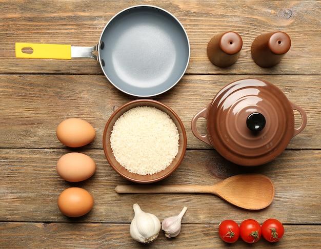 Ingredientes alimentares e utensílios de cozinha para cozinhar na mesa de madeira