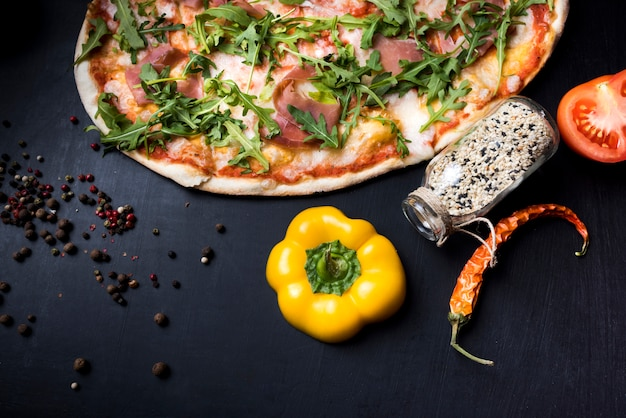 Ingredientes alimentares; especiarias e deliciosa pizza italiana em fundo preto de concreto