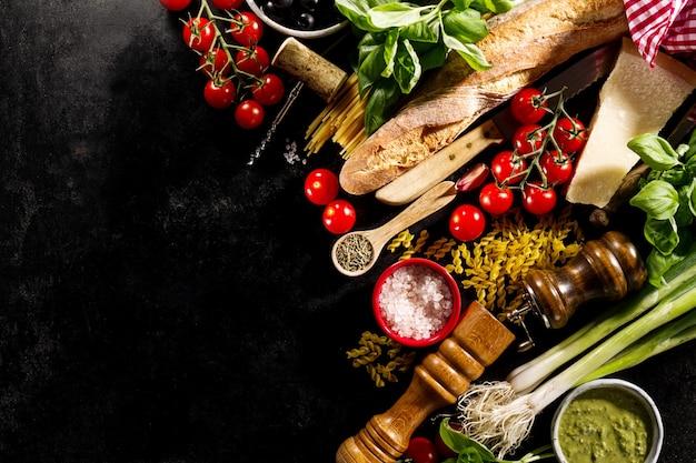 Ingredientes alimentares italianos deliciosos e deliciosos em fundo escuro.