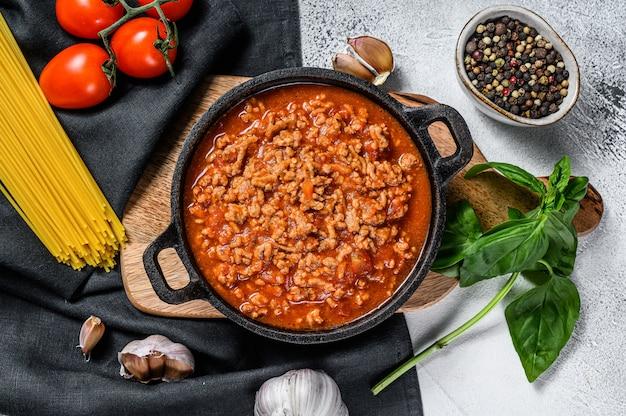 Ingredientes alimentares italianos para esparguete à bolonhesa. macarrão cru, manjericão, carne moída, tomate. fundo cinza. vista do topo