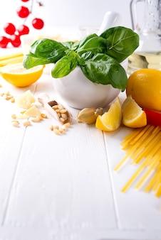 Ingredientes alimentares para massas italianas, espaguete em fundo branco de madeira.
