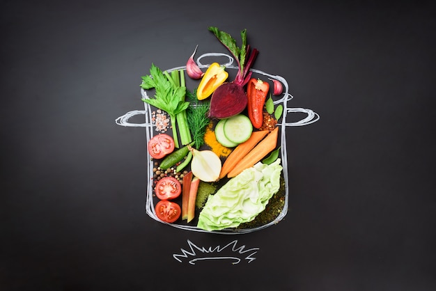 Ingredientes alimentares para misturar a sopa cremosa sobre stewpan pintado sobre quadro negro.