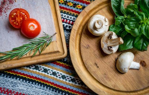 Ingredientes alimentares para pratos de pizza ou massa. tomates cereja frescos, cogumelos, folhas de manjericão, azeite