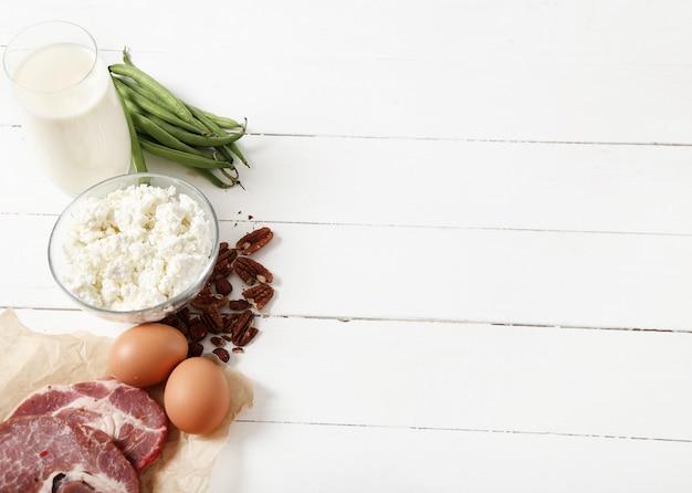 Ingredientes alimentares saudáveis na mesa de madeira branca