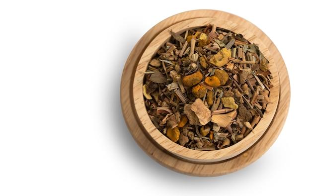 Ingredientes alternativos de ervas tailandesas para massagem e spa em uma tigela de madeira isolada no branco com traçado de recorte, erva seca