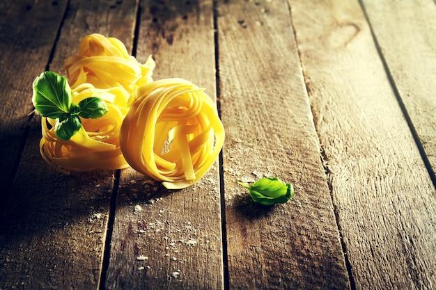 Ingredientes coloridos frescos saborosos para cozinhar tagliatelle da massa com manjericão fresco e tomates. fundo de madeira da tabela.