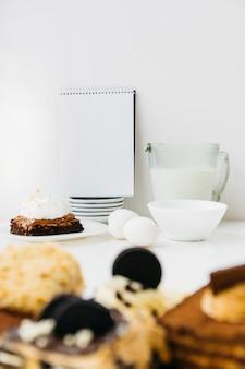Ingredientes com pastelaria e bloco de notas em espiral na placa