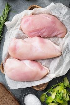 Ingredientes crus de frango crocante com alho em fundo cinza, camada plana
